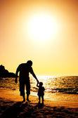 Vader en dochter spelen op het strand bij zonsondergang — Stockfoto