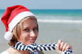 Christmas at sea. Girl in Santa hat on the beach — Stock Photo