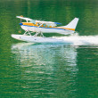 Aircraft seaplane taking off on calm water of lake — Stock Photo
