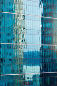 Reflections in modern glass-walled building facade — Stock Photo