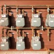 Natural gas meter bank on outside building wall - Stock Photo