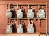 Natural gas meter bank on outside building wall — Stock Photo