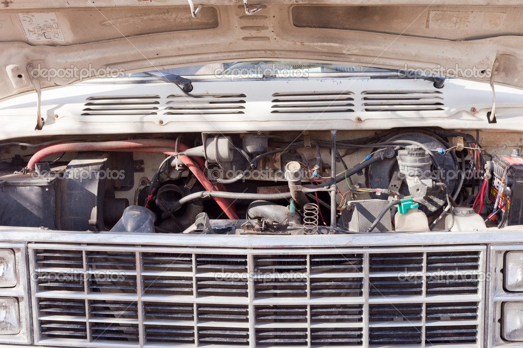 Front grille and confusing hoses and engine parts under open bonnet of old van — Stock fotografie #11130473