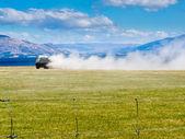 Truck spreading fertilizer on pasture meadow — Stok fotoğraf