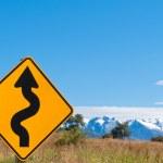 Wavy arrow roadsign and snowy mountain peaks — Stock Photo