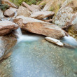 Small waterfall casdcading over rocks in blue pond — Stock Photo