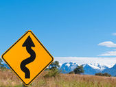 Wavy arrow roadsign and snowy mountain peaks — Stock Photo