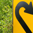 Stock Photo: Think green - U-turn roadsign in lush vegetation