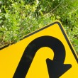 Think green - U-turn roadsign in lush vegetation — Stock Photo