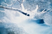 Small creek freezing up forming icicles — Stock Photo