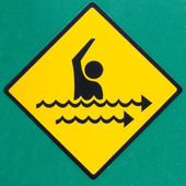 Rip current hazard symbol warning sign on green — Stock Photo
