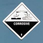 Corrosive hazard symbol warning sign on blue — Stock Photo