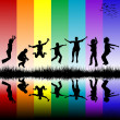 Group of children jumping over a rainbow striped background — Stock Photo