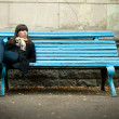 Stock Photo: Young womin black overcoat sitting on bench