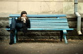 Young woman in black overcoat sitting on bench — Stock Photo