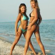 Two beautiful sexual girls pose on beach in swimsuit — Stock Photo