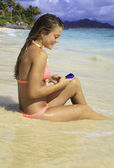Beautiful blond in bikini texting on the beach — Stock Photo