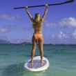 Beautiful girl in bikini on her stand up paddle board — Stock Photo #11659781