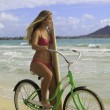 Girl with surfboard and bike on the beach - Stockfoto