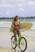 Girl with surfboard and bike on the beach — Stock Photo