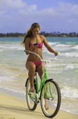 Girl on beach riding bike while texting — Zdjęcie stockowe