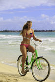 Girl on beach riding bike while texting — Stok fotoğraf