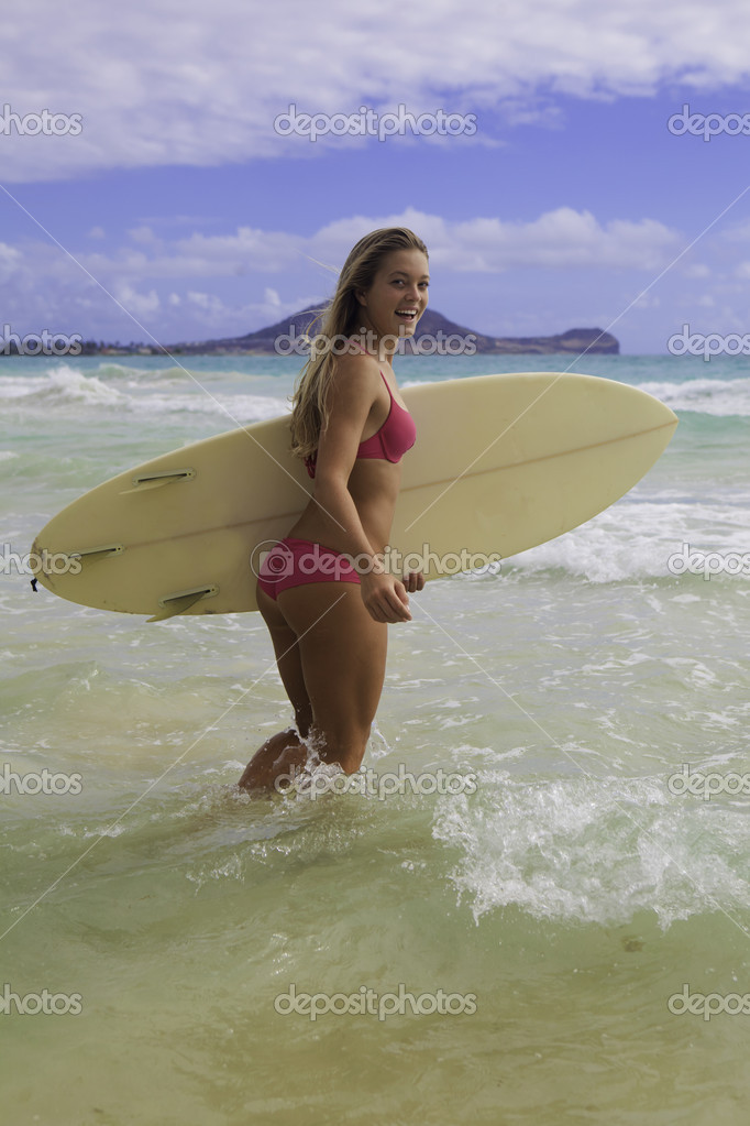 Blond girl in pink bikini walking into the surf with her board  Stock Photo #11962267