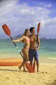 Couple with their kayak at the beach — Stock Photo