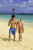 Couple walking on the beach with their paddle — Foto Stock
