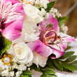 Gold wedding rings of groom and bride on bunch of flowers. — Stock Photo #10799865