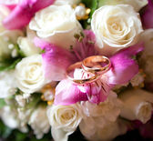 Gold wedding rings of the groom and the bride on a bunch of flowers. — Stock Photo