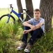 A teenager with a bicycle in the park on the grass — Stock Photo #11067712