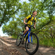 A teenager on a bicycle traveling in the woods - Stock Photo