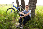 Um adolescente com uma bicicleta no parque na grama — Fotografia Stock
