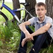 A teenager with a bicycle in the park on the grass — Stock Photo #11150350