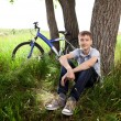A teenager with a bicycle in the park on the grass — Stock Photo #11150365