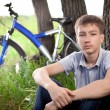 A teenager with a bicycle in the park on the grass — Stock Photo #11150374