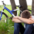 A teenager with a bicycle in the park on the grass — Stock Photo
