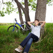 A teenager with a bicycle in the park on the grass — Stock Photo #11150409