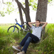 A teenager with a bicycle in the park on the grass — Stock Photo #11150437