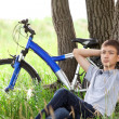 A teenager with a bicycle in the park on the grass — Stock Photo #11150450
