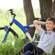 A teenager with a bicycle in the park on the grass — Stock Photo #11150467