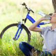 Stock Photo: Cyclist in park drinking clewater