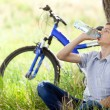 The cyclist in the park drinking clean water - Stock Photo