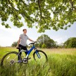 A teenager on a bicycle traveling in the forest - Stock Photo
