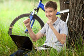 Teen in park with laptop — Stock Photo