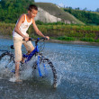 A boy rides his bike along the river — Stock Photo