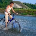 A boy rides his bike along the river — Stock Photo