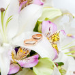 Gold wedding rings on flower — Stock Photo