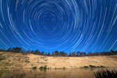 The motion of stars around the Pole Star in the background of the river — Stock Photo